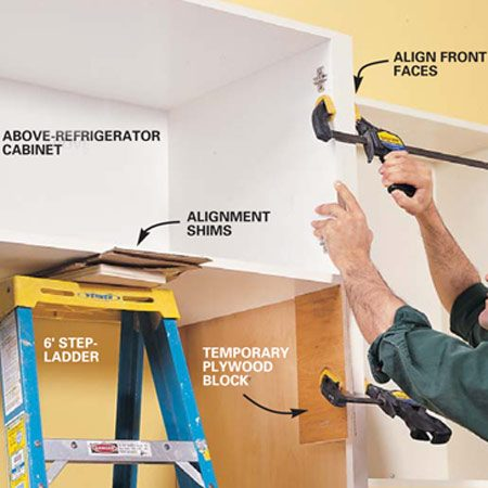 <b>Photo 12: Use support blocks </b></br> Support the refrigerator cabinet with a front support block clamped to the side panel and a stepladder below. Shim the cabinet to align with the top and face of the side panel. Screw the cabinet to the side panels and to the wall.