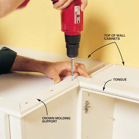 <b>Photo 13: Add crown molding support </b></br> Fasten the crown molding support to the top of the cabinets with 1-1/4-in. wood screws. If you have soffits, you'll need to fasten the supports from inside the cabinets or glue and shim them in place with construction adhesive or silicone adhesive. I like to position the supports so that the seam of the support and crown molding is hidden by the cabinet doors.