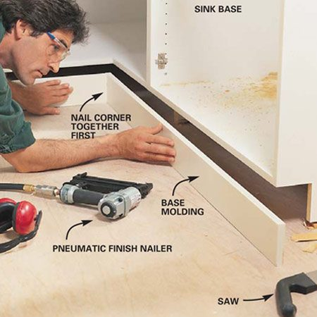 <b>Photo 15: Install the base kick panels </b></br> Fit the base molding to the base cabinets. You may wish to install your new flooring before you nail the molding in place. A pneumatic finish nailer really helps in this awkward position.