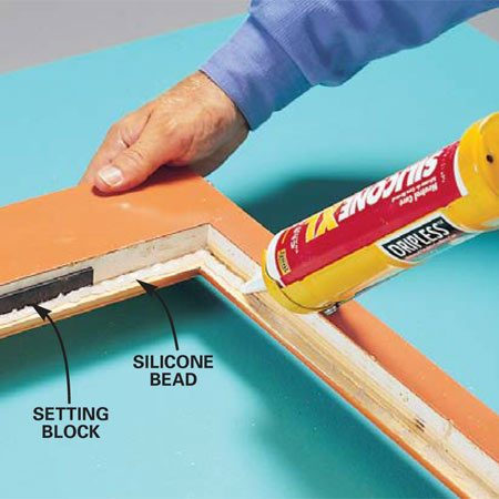 <b>Photo 5: Set the new glass in silicone</b></br> Apply a bead of clear neutral-cure silicone to the frame and drop in the new insulated glass. Make sure any setting blocks are properly positioned. Then run a thin bead of caulk along the backside of the stops and tack them in place with 3/4-in. brads spaced every 6 in. Let excess caulk dry, then scrape it off with a razor scraper.