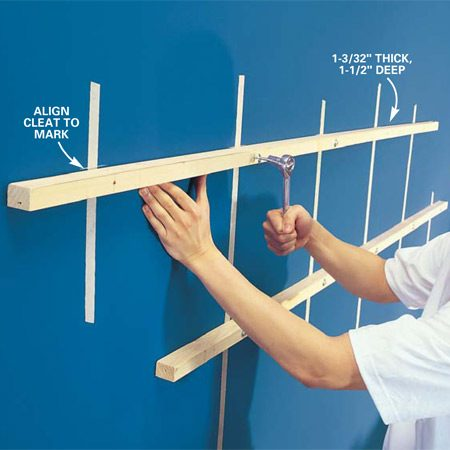<b>Photo 4: Screw the cleats to the wall</b></br> Predill 1/4-in. dia. holes at the stud locations after you cut the cleats to length (the measurement between the end blocks of the door half). Hold the cleat to your line on the wall and drill into the stud with a 1/8-in. bit. Using a wrench, install one lag screw into each stud until it's tight. Use 1/4-in. x 3-1/2 in. lag screws. Each cleat must be straight as an arrow.