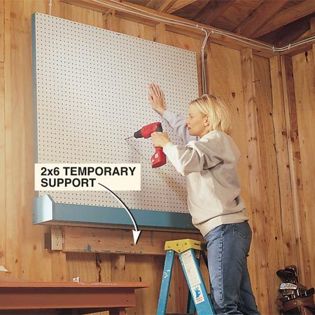 <b>Photo 4: Install the board and bin</b></br> Fasten the pegboard to the wall with 3-in. drywall screws driven through the frame into the wall studs.
