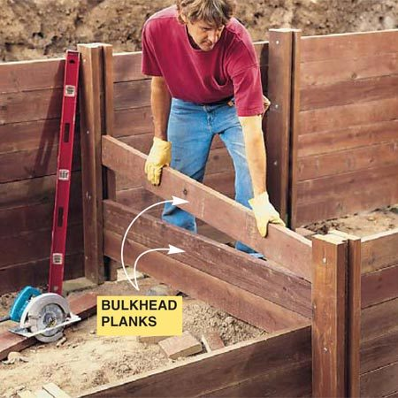 <b>Photo 15: Add bulkheads as needed</b></br> Slip the first bulkhead plank into the stanchion recesses, then level and nail through the outside corners of the 2x6s. Drop in and nail the rest of the bulkhead planks.
