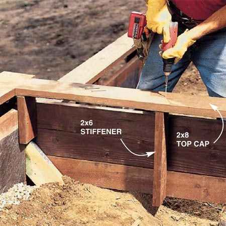 <b>Photo 16: Install 2x8 cps</b></br> Screw the 2x8 top caps to the top of the stanchions with two 3-in. deck screws at each post. For bulkhead spans longer than 4 ft., nail a vertical 2x6 stiffener to the backside of the wall planks. It'll keep the wall planks in line and add strength to the top cap in case someone uses it for a step.