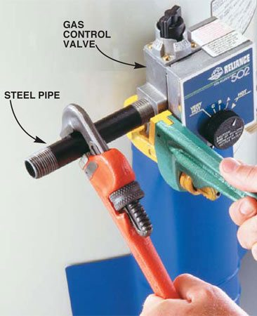 <b>Photo 8: Use two wrenches to attach the gas line</b></br> Reconnect the gas line. Coat the threaded ends with pipe joint compound and screw the first nipple into the gas valve. Use two pipe wrenches to avoid stressing the valve. Reassemble the remaining nipples, finishing up with the union (Photo 2). Then follow these four steps to fill the tank: (1) Close the drain valve; (2) turn the water back on at the main shutoff and open the cold water valve to the water heater (leave it open); (3) turn on a nearby hot water faucet until water comes out; and (4) inspect all the joints and fittings for water leaks.