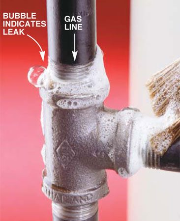 <b>Photo 9: Look for bubbles at connections</b></br> Turn on the gas and check connections for leaks by brushing a 50-50 mixture of dishwashing liquid and water over the joints. If the mixture bubbles, you have a leak. Tighten or reconnect joints that leak. Wipe the joints dry when finished. Call the plumbing inspector to check over your work.