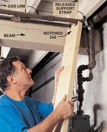 <b>Photo 2:  Separate pipes from the beam</b></br> Release all rigid connections between gas, heating, plumbing or electrical lines (in conduit) and the house beam. To avoid rupturing these lines while the beam is being raised, support them with a 2x6.