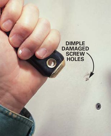 <b>Photo 4: Make a dimple in damaged drywall holes</b></br> Remove any fasteners that have broken through the paper surface or missed the framing, and drive a replacement screw above or below the location into solid wood. Slightly dent the damaged paper left from extracted fasteners by tapping the spot with the butt of the knife handle.