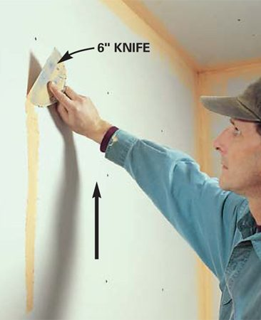 <b>Photo 8: Fill nail or screw holes </b><br/>Fill fastener holes by spreading a narrow band of mud upward over a column of screw- or nailheads with the edge of the 6-in. knife.