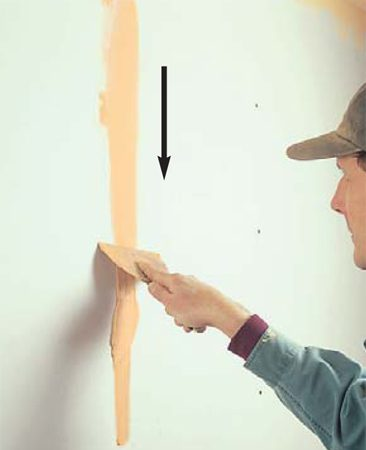 <b>Photo 9: Scrap away excess mud </b></br> Drag the end of the knife over the filler swipe to scrape away all of the surface mud. Use this technique at the end of each of the three coats to fill and refill all the fastener holes.