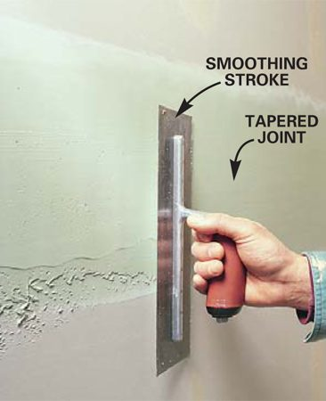<b>Photo 13: Coat the tapered joints </b></br> Lay the second coat on tapered joints using the same technique demonstrated in Photo 11, but keep the entire width of this coat only a few inches wider than the length of the trowel.