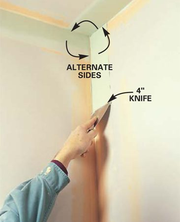 <b>Photo 14: Spread the second coat over one side of angles</b><br/>Spread a thin layer of mud over one side of vertical and ceiling angles with a 4-in. knife. Apply more pressure to the outside of the knife blade to wipe off excess mud and leave a feathered edge. Refill fastener holes (as in Photos 8 and 9).