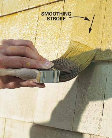 <b>Photo 6: Work the paint in with a brush</b></br> Back-brush by working the paint into cracks and onto the bottom edge of shingles and siding with your paintbrush. Then brush with the grain of the wood to smooth the paint.
