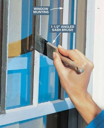 <b>Photo 9: Paint onto the glass</b></br> Lap paint slightly onto the glass as you paint window muntins and sash. Use a 1-1/2 in. angled sash brush. Wipe off most of the paint on the edge of the can for better control. After the paint dries, scrape the excess from the glass with a single-edged razor blade.