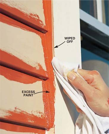 <b>Photo 13: Wipe mistakes while they're wet</b></br> Wipe excess paint from the face of the window trim with a rag before it dries. Use this same tip anywhere excess paint builds up along an edge.
