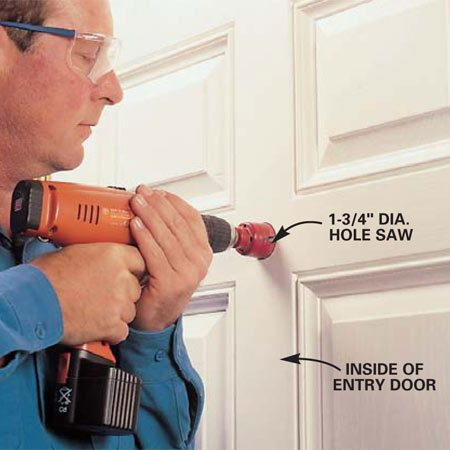 <b>Photo 1: Bore the hole</b></br> Mark the viewer's position on the door, preferably centered in the door stile near eye level. Bore the hole with a hole saw, holding the drill straight and level and starting it on low speed. Prevent splintering the outside door veneer by occasionally stopping the drill and checking the other side of the door so you'll know the moment the pilot bit first emerges.
