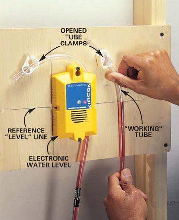 <b>Photo 4: First calibrate</b></br> Calibrate an electronic water level by first attaching it plumb and level to a plywood scrap. Fill the tube with water and bleed air out of the line. Calibrate by loosening both tube clamps, turning on the electronic level and raising the working tube to the reference line. The unit's horn should sound as the water in the working tube touches the reference line.