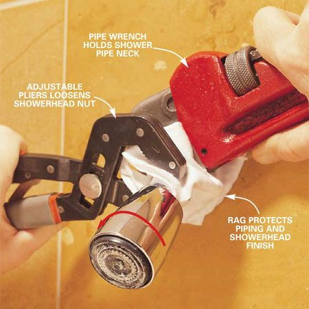 <b>Photo 1: Protect the finish when removing the showerhead</b></br> Unscrew the showerhead by gripping the shower neck with a pipe wrench (as shown), grabbing the nut on the showerhead with the adjustable pliers and turning pliers counterclockwise until the nut loosens. Protect the finishes on the showerhead and wall pipe by wrapping them with a cloth.