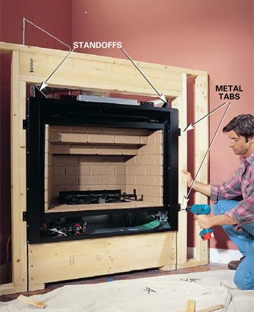 <b>Photo 13: Build the wall surrounds</b></br> Build the wall that surrounds the fireplace using Fig. A as a guide. Allow 1/2 in. of space between the wood framing and the fireplace on both sides. Screw the metal tabs on the fireplace to the wood frame to secure it.