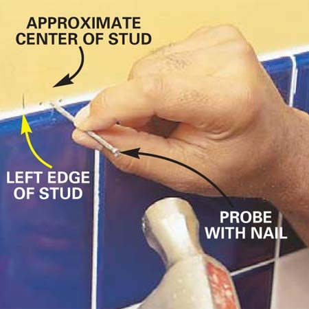 <b>Photo 2: Mark the sides of the studs</b></br> Find the edges of the studs by probing with a finish nail. Make a series of holes in an inconspicuous location, like directly above the tile, and mark both edges of the studs.