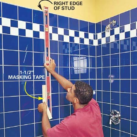 <b>Photo 3: Transfer the stud locations to the tile</b></br> Extend the stud marks down to the grab bar location with a level. Place a strip of 1-1/2 in. masking tape on the tile to indicate the studs.