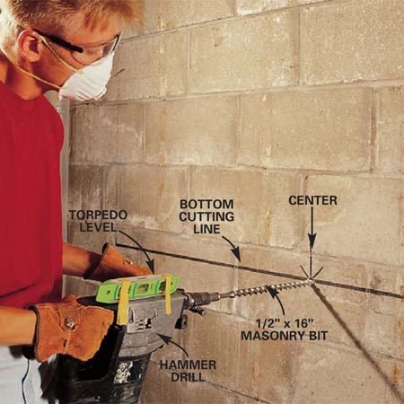 <b>Photo 4: Drill a pilot hole </b><br/>Measure down from the joists to locate the height of the bottom cut. Mark the center of the bottom cutting line and drill a level pilot hole with a hammer drill and a bit long enough to go through the wall.