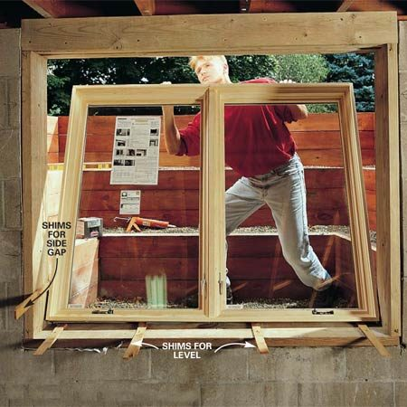 <b>Photo 15: Install the window </b></br> Center the window in the opening and level it with cedar shims. Get help here to steady the window while you shim it. Temporarily tack the shims in place and remove the window.