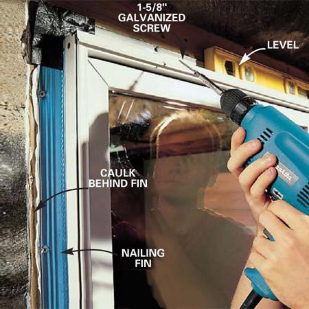 <b>Photo 16: Caulk around the window </b><br/>Apply a generous bead of caulk around the treated wood frame to create a seal behind the nailing fin of the window. Set the window in place, check it for level, and drive screws or nails through the nailing fin to secure it to the frame. Some manufacturers specify that the fin must be nailed, not screwed.