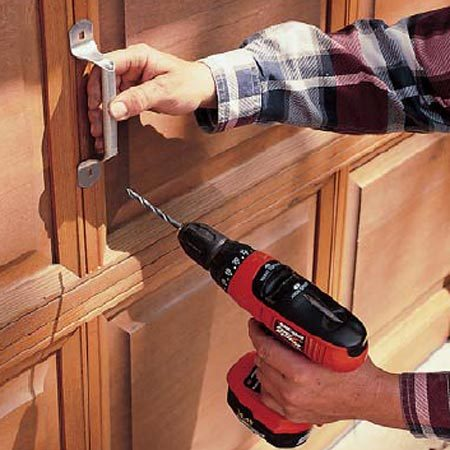 <b>Photo 9: Install lift handles</b></br> Install a lift handle on both sides of the door. Make sure the handle will clear the top of the door frame; otherwise, you may need a lower-profile handle or your door may need adjustment. If there's a handle, you're less likely to pull down on the spaces between sections, a habit that results in hundreds of crushed fingers every year.