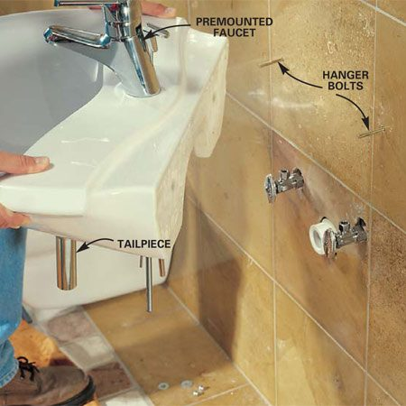 <b>Photo 21: Install the sink </b></br> Install the faucets and tailpiece in the sink before mounting. Mark the mounting holes on the wall and drill 5/16-in. holes through the tile and cement board and 1/4-in. holes into the backer boards. Screw the hanger bolts through the tile into the wood using the cap screw to drive the bolt. Slip the sink over the screws and snug down the nut.