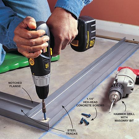 <b>Photo 2: Layout and fasten the tracks</b></br> Fasten steel tracks to concrete using 1-1/4 in. hex-head concrete  screws. Lay out the position of the track, strike chalk lines, and drill a hole  through the metal and into the concrete the full length of the screw. Use a  hammer drill fitted with a carbide tipped masonry bit. Set screws first at each  end of the track and then every 3 ft. along the track. Overlap track corners by  notching the first track's flange so the overlapping track can slide into  place. On long, straight runs, overlap adjoining tracks 6 in. and secure the  overlap to the floor with a concrete screw.