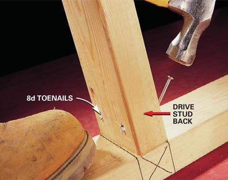 <b>Photo 3: Nail from the other side</b></br> Drive toenails into the opposite side to complete the toenailing and at the same time drive the board back to the layout line.
