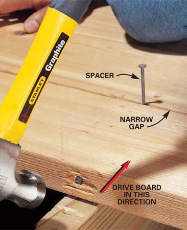 <b>Photo 5: Drive the nail and board straight</b></br> Pound the nail with heavy hammer blows to straighten the deck board and close the gap between the two boards. Use a shim or nail to maintain a consistent space between boards.