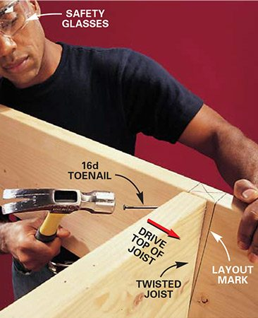 <b>Photo 6: Straighten twisted joists</b></br> Move twisted framing members into alignment by toenailing in the direction you want the board to go. Continue pounding on the nail until the board is in the desired location. Add a second toenail to move the board farther if necessary.