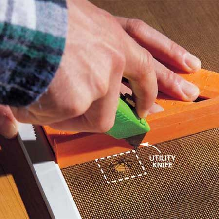 <b>Photo 1: Cut out the hole</b></br> Cut a square hole around the tear using a straightedge and sharp utility knife. Keep the hole as small as possible and leave at least 1/2 in. of old screen next to the metal frame.