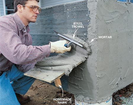 <b>Photo 10: Spread mortar on lath</b></br> Mix the mortar according to the directions on the sack and scoop it onto a hawk. Hold the hawk against the wall, and slide the mortar onto the wall with a steel trowel. Firmly press the mortar into the lath, completely covering it by a good 1/8 in. Work fast. Have a helper mix mortar while you spread it.