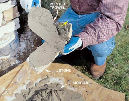 <b>Photo 14: Back butter</b></br> Butter each stone by spreading mortar on the back. Press the mortar into the pores of the stone as you draw the trowel toward you, drawing off the excess.