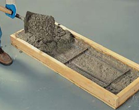 <b>B: Add concrete</b></br> Fill the forms one-third full with concrete, drop in the rebar, then finish filling the forms. Work the concrete into the corners and sides with the blade of the shovel as you go.
