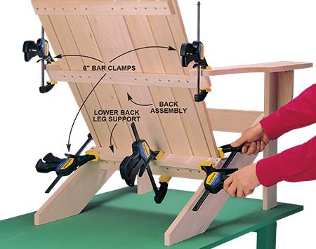 <b>Photo 7: Fasten the back to the legs</b></br> <p>Glue, clamp and screw the lower back leg support (M) to the back legs first. Then glue and clamp the back assembly, first to the back legs, then to the arm supports. Drill pilot and countersink holes for the screws.</p>