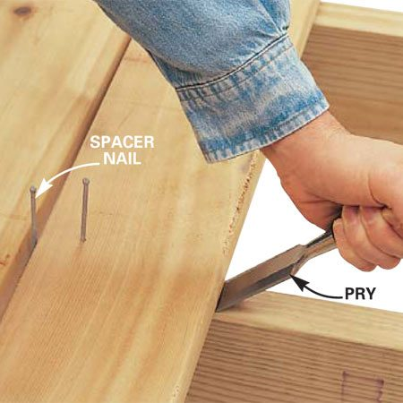 <b>Lever the board tight to the spacer</b></br> Drive a chisel into the joist and lever the board toward you. When the board is tight to your spacer, nail the board to the joist.