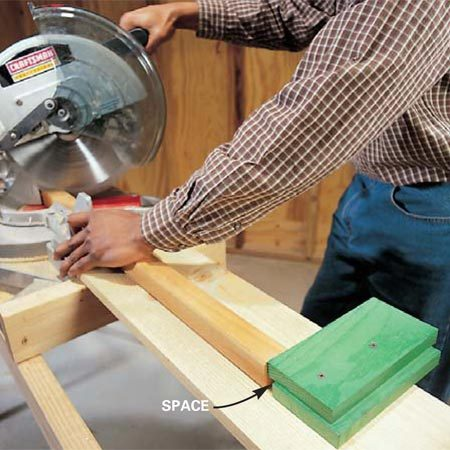 <b>Photo 4: Use stop blocks for repeat cuts </b><br/>Screw two blocks of wood to the miter saw stand to act as a stop for repetitive cutting to the same length. Set the lower block back about 1/2 in. so that if sawdust or wood chips pile up against it, they won&#39;t affect the cutting length.