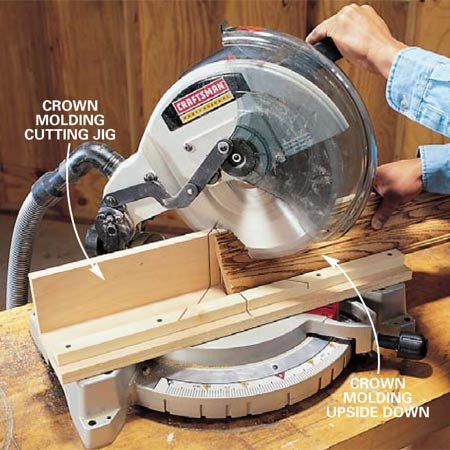 <b>Photo 6: Fasten the jig to the fence </b></br> Attach the jig with 3/4-in. screws through holes in the miter saw fence. Cut miters with the crown molding upside down.