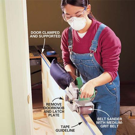 <b>Photo 3: Sand the edge</b></br> With the door installed, mark the trim line with tape, using the jamb as a guide. Then remove the door, support it, and sand down to the tape with a belt sander.