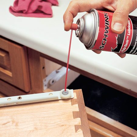 <b>Photo 2: Wipe and lubricate</b></br> Wipe old lubricant and dust from all drawer and cabinet rollers and guides. Squirt new lubricant into all four roller assemblies. Wipe excess lubricant off with a rag and reinstall the kitchen drawers by reversing the steps in Photo 1.