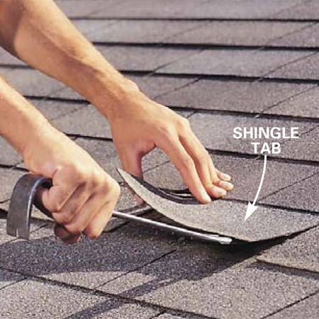 <b>Photo 1: Loosen the tabs</b></br> Lift the shingle tabs that are centered over the porch stoop by gently pushing the flat end of a pry bar under each tab. If the asphalt sealant holding the courses of shingles together won't release, apply more force to the pry bar by punching the back of the bar using your palm or tapping the bar <em>lightly</em> with a hammer. Work in temperatures of about 40 to 70 degrees F.