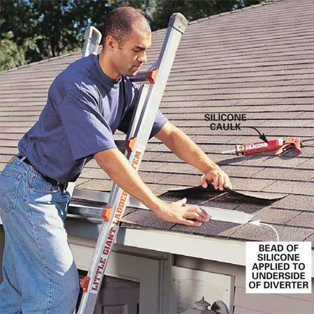 <b>Photo 2: Slide the diverter in</b></br> Apply a 1/4-in. thick bead of clear silicone caulk on the <em>underside</em> of the drip edge, lift the shingle tabs up slightly and slide the diverter under the tabs. Slide one end of the diverter tight to the bottom of the shingle tabs and leave a 1-in. exposure at the other end to create a drainage pitch.