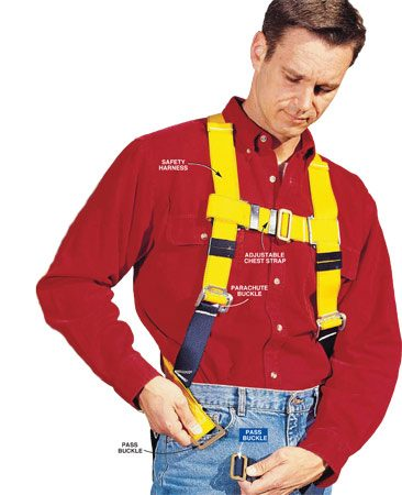 <b>Photo 3: Putting on the safety harness</b></br> Strap on the safety harness according to the manufacturer's instructions. Tighten the straps for a snug fit. Double-check all the buckles before you go onto the roof.