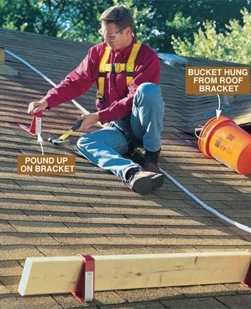<b>Photo 6:</b><br/>Relocate or remove brackets by pounding up to slide them off the nails. Keep the lowest set of planks in place until you're done on the roof. Store tools and supplies in a bucket hung from a roof bracket.