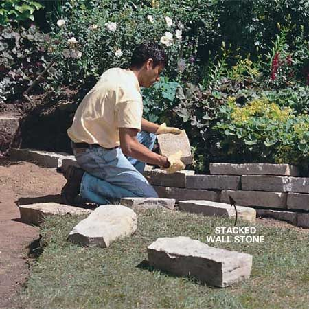 "<b>Photo 4: Stagger the wall stones </b></br> Stack the stone for the low retaining wall on the compacted gravel base. Stagger the joints in the stones and set each row back 1/2 in. behind the face of the stones below so the wall ""leans into"" the hill. Pack soil behind the stones as you build the wall."