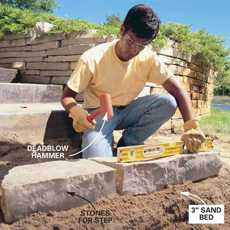 <b>Photo 6: Form the front of the step </b></br> Set 6 x 8-in. wall stone into a 3-in. bed of sand to form the step. Settle and level the stones with a rubber mallet or a hammer and block of wood. Then fill behind the step stones with packed sand and set the path stones even with the top of the step.